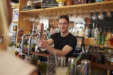 Bartender Serving Customers In Busy Bar