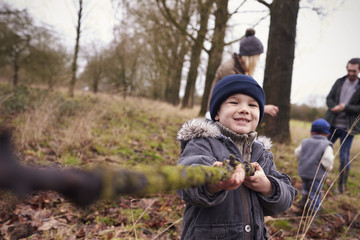 Young Boy Holding Stick On Family Winter Walk