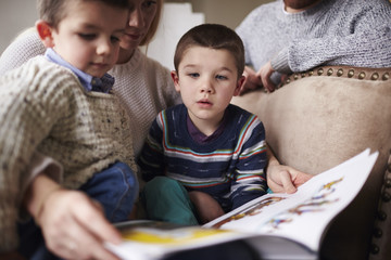 Mother reading story book for sons at home