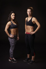 Two athletic women in sports clothing, full length portrait