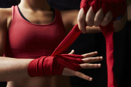 Midsection of woman wrapping her hand for boxing training