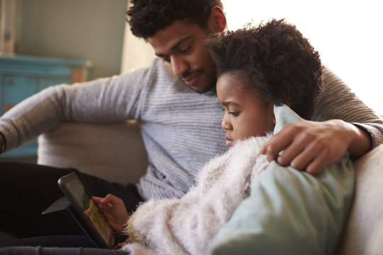 Father and daughter using digital tablet at home