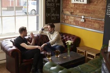 Two Male Friends Enjoying Drink In Bar Sitting On Sofa