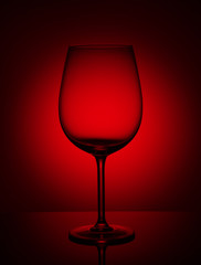 Empty wine glass on a red background.