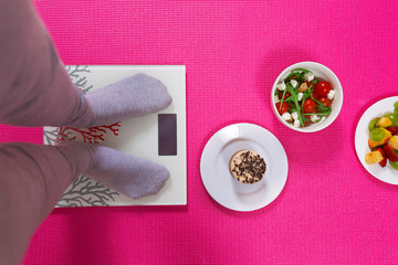 Close-up of female legs on weight scale surrounded by plates with various types of food