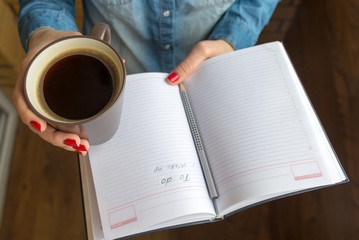 female hands holding a cup of hot coffee and notebook