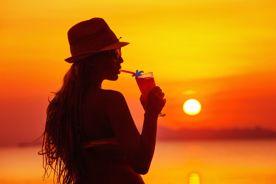 Closeup portrait of woman in hat with cocktail at tropical sunset