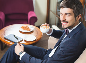 Handsome male has a french breakfast at cafe restaurant