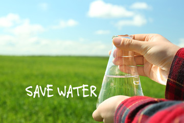 Female hands with flask and Save Water text on natural background