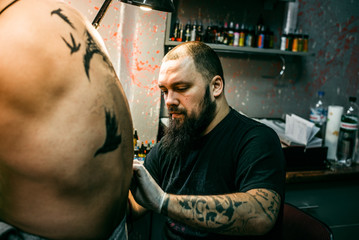 the process of creating a tattoo on the back of a man
