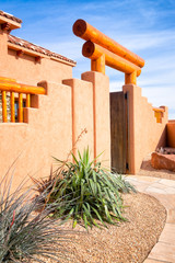 American Southwest style adobe architecture entry gate with heavy wood beams