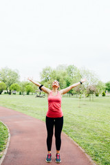 Happy successful fitness woman raising arms and winning