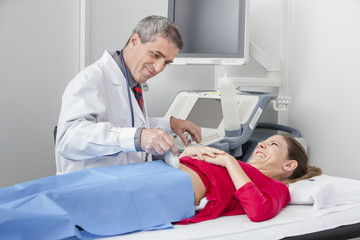 Doctor performing ultra sound on new mother