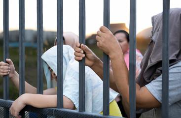 Refugee peoples hand holding metal bar on refugee camp site  sit