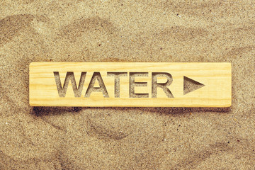 Water direction sign in dry desert sand