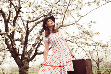 female in vintage clothes with suitcase in cherry blossom