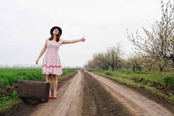 woman in vintage clothes with suitcase in field. Vintage toning
