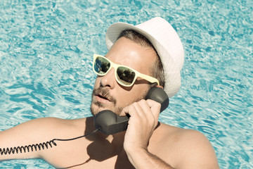 Close up of a young man using a retro styled handset in the swimming pool