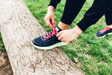 Woman tying shoelaces in nature
