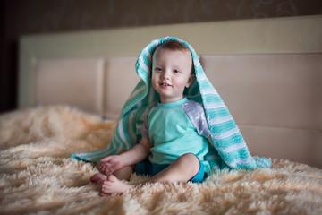 little boy hiding under a blanket