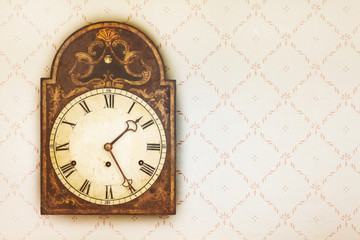 Vintage clock on a wall with retro wallpaper