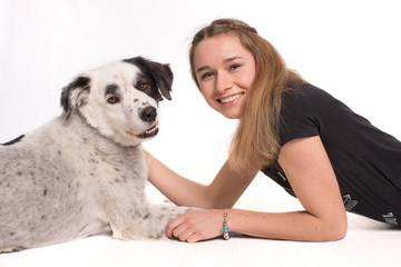 Lächelndes Mädchen mit ihrem Hund in Bauchlage- freigestellt-
