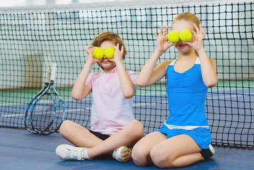 children having fun and playing on the tennis court