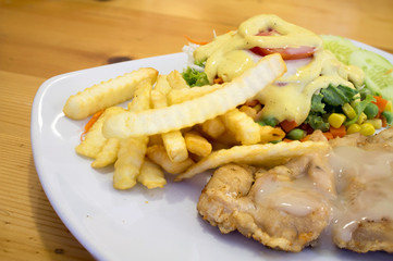 chicken steak with sauce, french fries and salad [blur and select focus background]