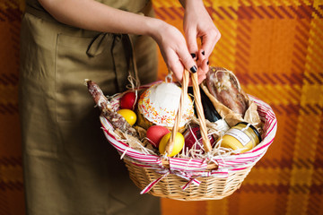 Female hands holding basket with colorful eggs, cake, red wine, hamon or jerky and dry smoked sausage. Food gift set for celebrating Easter.