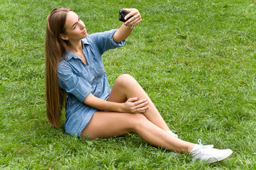 Young beautiful girl on the nature of the photographs herself