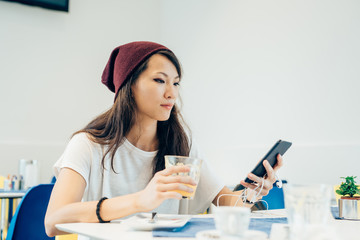 young handsome asiatic  woman sitting in a bar, holding a smart phone and glass of juice, looking down and tapping the screen - technology, social network, communication concept