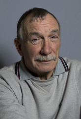 Portrait image of a happy mature man. Studio shot taken on a grey background.
