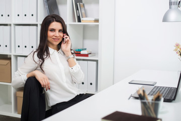 Business woman with notebook in office, workplace, talking on phone
