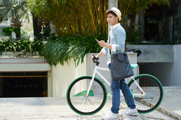 Smiling stylish man walking with bicycle in the city