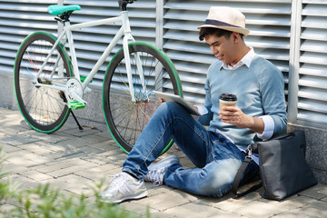 Smiling Asian guy sitting outdoors and using app on tablet