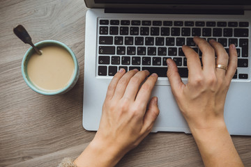 Laptop and coffee cup in girl's hands sitting on a wooden backgr