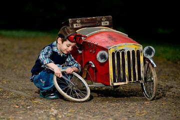 Small boy repair red car