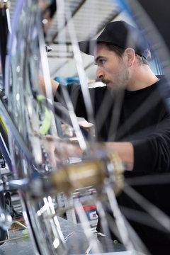 Side view of bearded man constructing bike