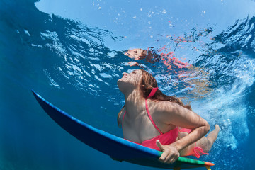 Young girl in bikini in action - surfer with surf board dive underwater with fun under big ocean wave. Family lifestyle, people water sport lessons, beach extreme swimming activity on summer vacation