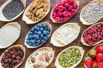 Superfood, detox, dieting food.Berries, seeds, nuts, fruits top view on wood background.