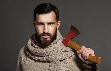 Handsome male lumberjack is standing and holding a hatchet. He is looking at the camera with threats and seriousness. He has beard