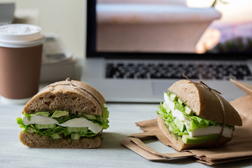 Sandwich with mozzarella, avocado, cucumber, salad and pesto