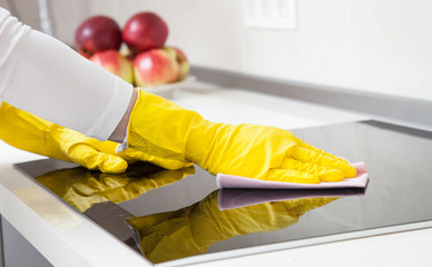 Housewife cleaning an induction plate