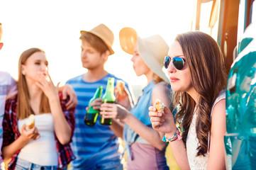 Group of teenage hipsters on roadtrip, drinking beer, eating