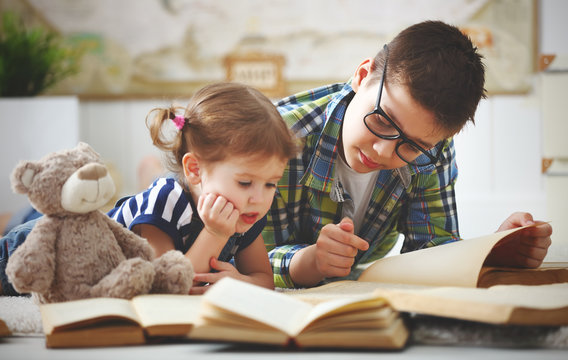children brother and sister, boy and girl reading a book