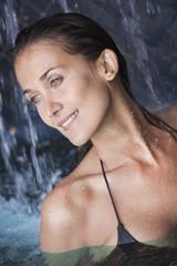 belle femme souriante sous une cascade d'eau dans une piscine