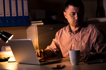Young businessman working late on laptop at night in dark office