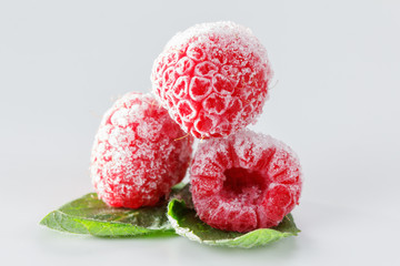 Frozen raspberries with mint leaves on white