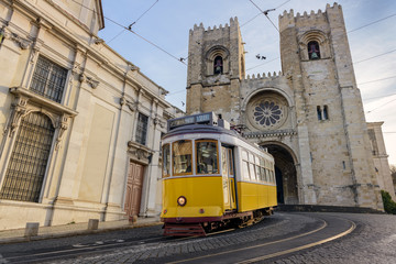 A famous yellow tram 28 passing in front of Santa Maria cathedral, Lisbon, Portugal