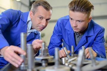 Technician appraising mechanical parts
